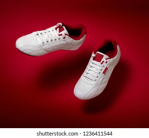 White sneakers floating over red background with copy space for text.