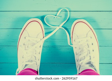 White sneakers with heart on blue wood background, filtered image