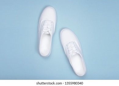 White sneakers on blue background, flat lay.Fashion trend shoe,  concept shoe shop