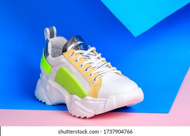 White sneakers on blue and pink background. Creative sport footwear design concept. Women or teenager shoes.