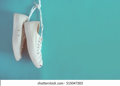White sneakers on light blue background.Toned image.