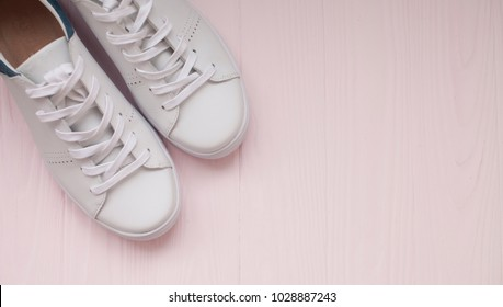 White sneakers on light pink background.Toned image. Women's shoes.  stylish white sneakers