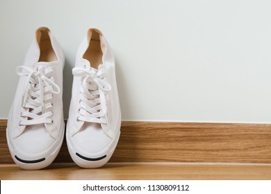 White sneakers on wood background, concept Copy space