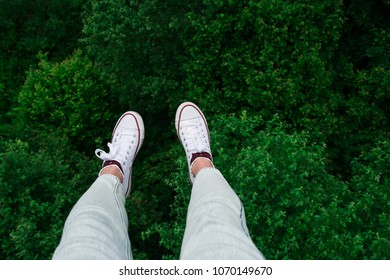 White sneakers over green tree crowns