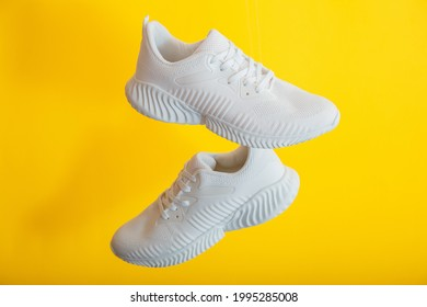 White sneakers shoes fly on yellow color background. Pair of sport male sneakers. Levitation footwear on yellow wall
