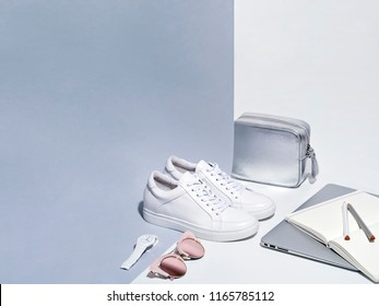 White sneakers sunglasses watch silver handbag laptop open sketchpad and pencils on white and gray background.
