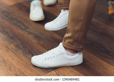 White sneakers,lower half, legs, on wooden boards.