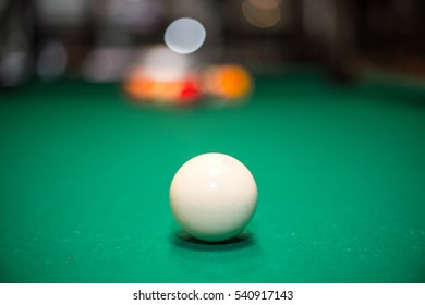 White snooker ball on the pool table with light bokeh in background