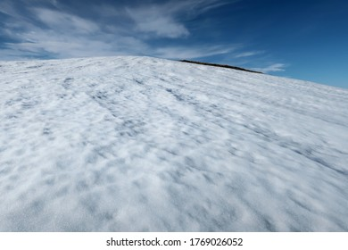White snow and blue sky - cold summer in Chukotka, Far East Russia