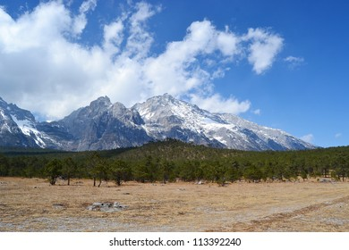 white snow mountain with forest with blue sky and cloud background , Jade Dragon Snow Mountain or Mount Yulong in Lijiang country, Yunnan province