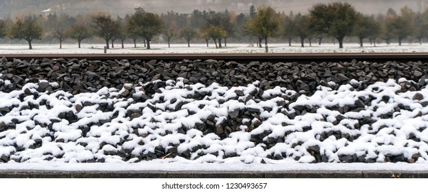 white snow on railroad tracks and rocky embankment shoulder with snow covered fields and tree orchard behind