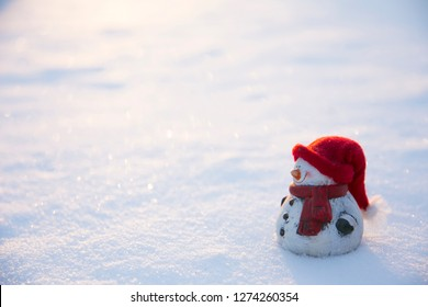 White snowman figure with warm hat and scarf standing in snow, sun setting outdoors in winter, lot of copy space.