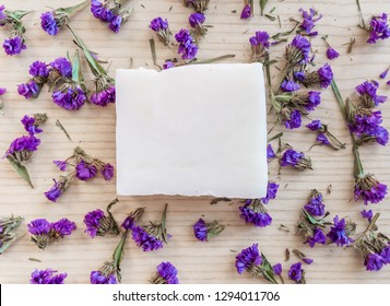 White soap bar on a wooden background with violet flovers top view. Pure natural soap with cedar oil and herbal ingredients. Handmade natural cold process soap. Eco-friendly exfoliating soap for hair