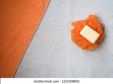 White soap on an orange washcloth on a background of bright towels.