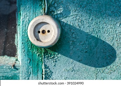 White socket on the outside of the wooden wall of a house painted in green and turquoise colors. The paint is cracked and peeling. The texture of a bad condition and quality.