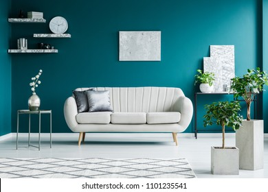White sofa between a metal table and a black desk with paintings and plant in a turquoise living room interior