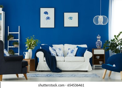 White sofa and blue armchairs in cozy living room