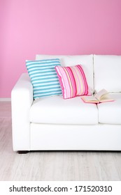 White sofa close-up in room on pink background