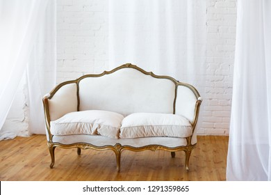 White sofa with fabric upholstery in a room with wooden floor and white curtains