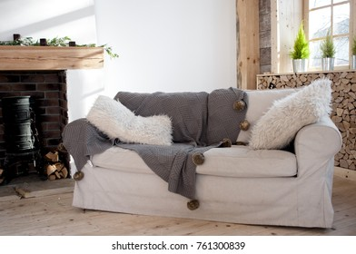 white sofa with fluffy pillows and a coverlet with pompoms near the fireplace, Scandinavian style
