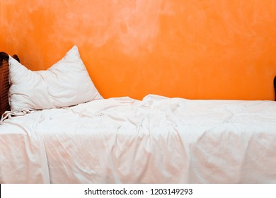 White sofa in front of orange wall