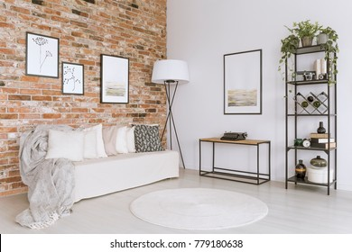 White sofa with pillows and white carpet in living room with lamp against red brick wall with gallery