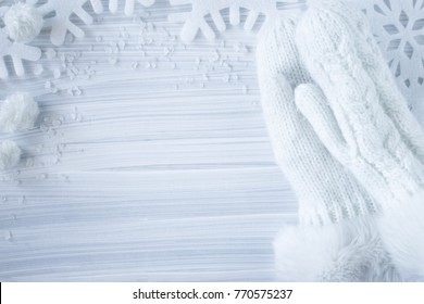White, soft and fluffy knitted womanly mittens with snowflakes on the wooden background. Warm mittens protecting hands from cold winter. Winter time wear concept. Empty place for a text.