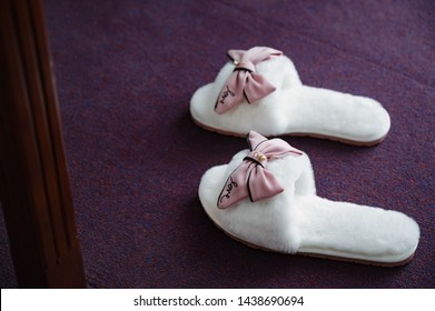6bdddaf23 White soft women's slippers stand in the bedroom close up. House slippers  for home