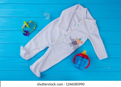 White soft wool baby pajama with toys. Footie clothes, pacifier, bottle and rattle. Blue wood background.