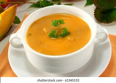 a white Soup cup with fresh pumpkin soup