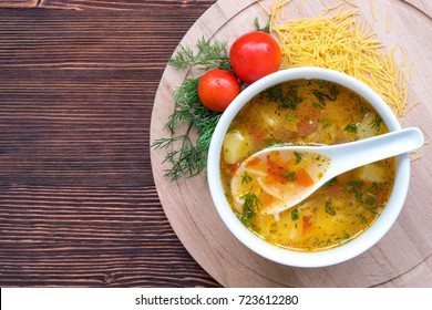 White soup noodles with tomatoes. Potatoes, dill, spices. On a wooden Board.