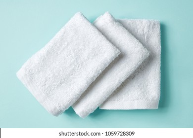 White spa towels on light blue background, top view