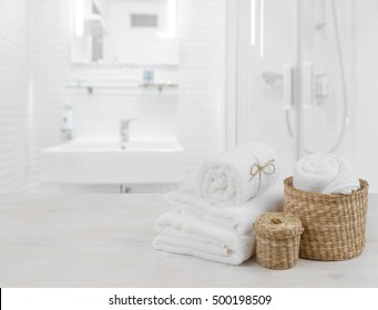White spa towels and wicker baskets on defocused bathroom interior