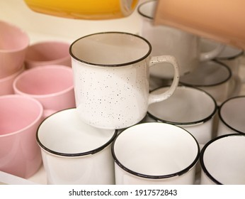 White speckled glaze mug at store selective soft focus. Empty ceramic coffee cup in supermarket. White cups with black dots. Clean white mugs. Cozy home crockery concept.