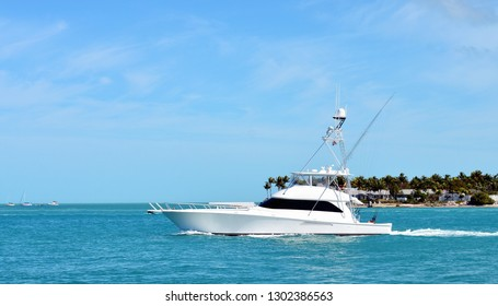 A white sport fishing yacht passing Sunset Key in Key West Harbor on the way to the Atlantic Ocean to go fishing.