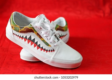 White sport shoes on red background