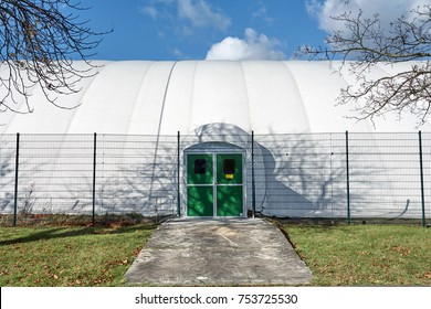 White sports hall dome - Entry Door - Under a blue cloudy sky