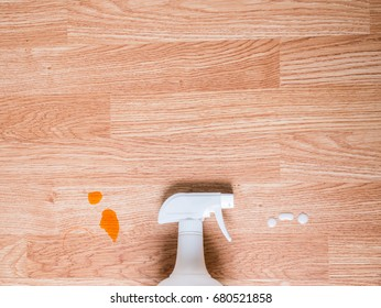 White spray bottle cleans stain on wooden table for cleaning concept or advertising