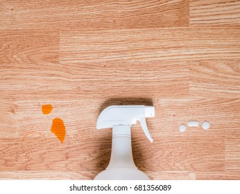 White spray bottle cleans stain in close up view on wooden table background for cleaning concept or advertising