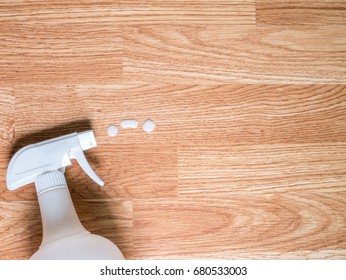 White spray bottle spraying on wooden table background for cleaning concept