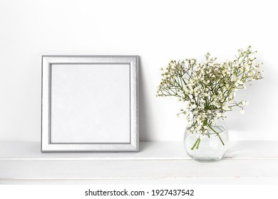 White spring flowers in a glass vase with a silver photo frame on a white table. Cozy white interior.