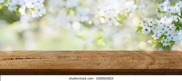 White spring flowers in a park with empty rustic wooden table for an easter background