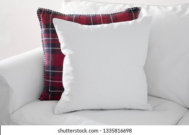 White square cushion with red plaid cushion on a white sofa.