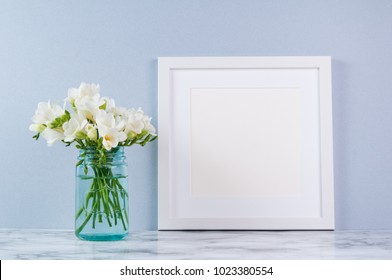 white square frame mock up with white fressia flower bouquet in a blue glass jar