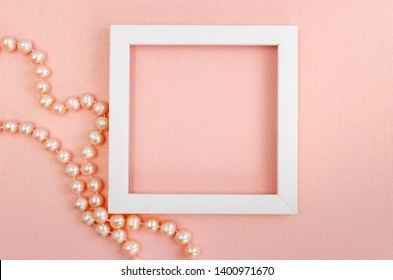 White square frame with pearl beads on a pink pearl design board. Background, paper texture pink color