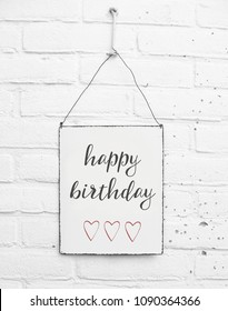 White square metal plate on white brick background - mock up template - Happy birthday - Party celebration