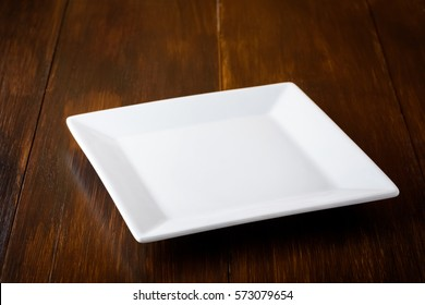white square plate on a wooden table