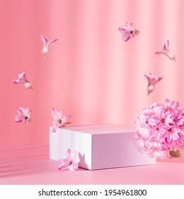 White square podium group for display cosmetic and goods with fresh spring flowers hovering as frame in sun beam on gentle pastel pink background, modern fashion style.