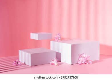 White square podiums group for display cosmetic and goods with fresh spring flowers in sun beam on gentle pastel pink background, modern fashion style.