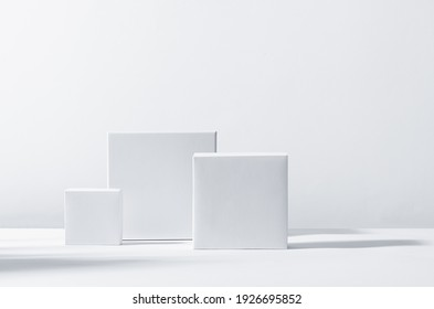 White square podiums in sunlight with shadow on white background. Trend fashion showcase for cosmetic products, goods, shoes, bags, watches. - Shutterstock ID 1926695852